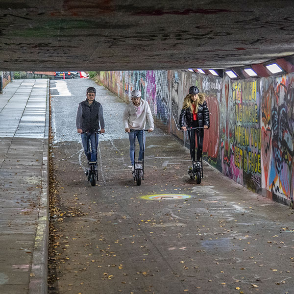 Three people ride Autokraft electric scooters down underground tunnel