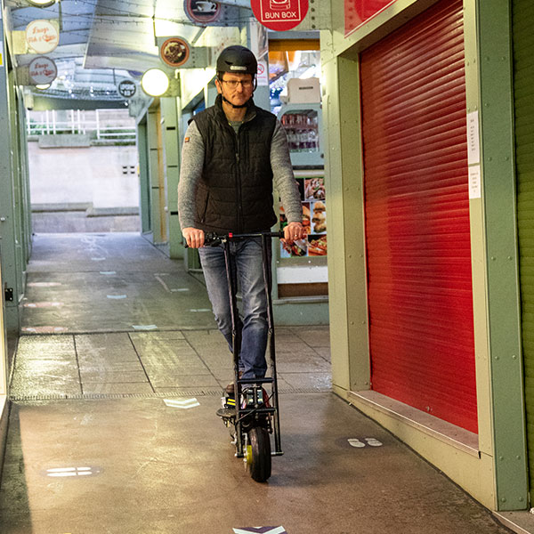 Man rides Autokraft TR-560 scooter in Norwich Market